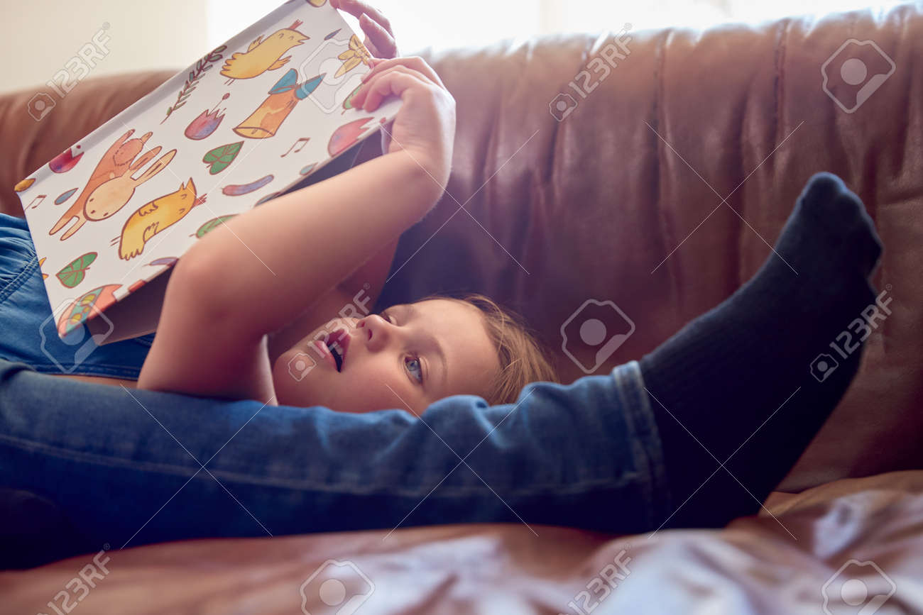 Close Up Of Father And Daughter Lying On Sofa At Home As Girl Reads Book - 172365099