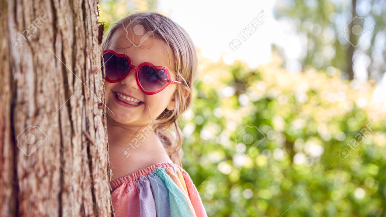 Smiling Young Girl Wearing Sunglasses Playing Hide And Seek Behind Tree In Garden - 172365102