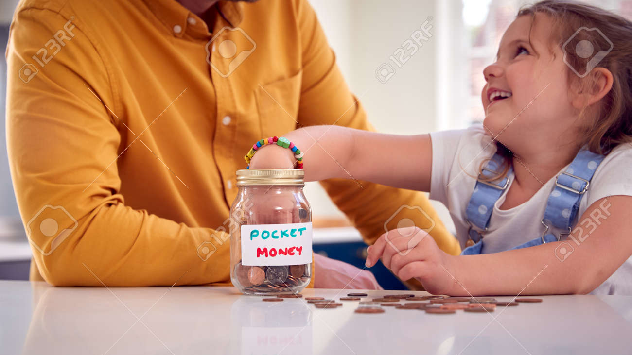 Close Up Of Father And Daughter Counting Pocket Money In Jar On Kitchen Counter - 172365104