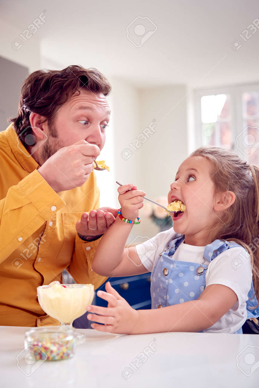 Father And Daughter In Kitchen Eating Ice Cream Dessert With Spoon - 172365302