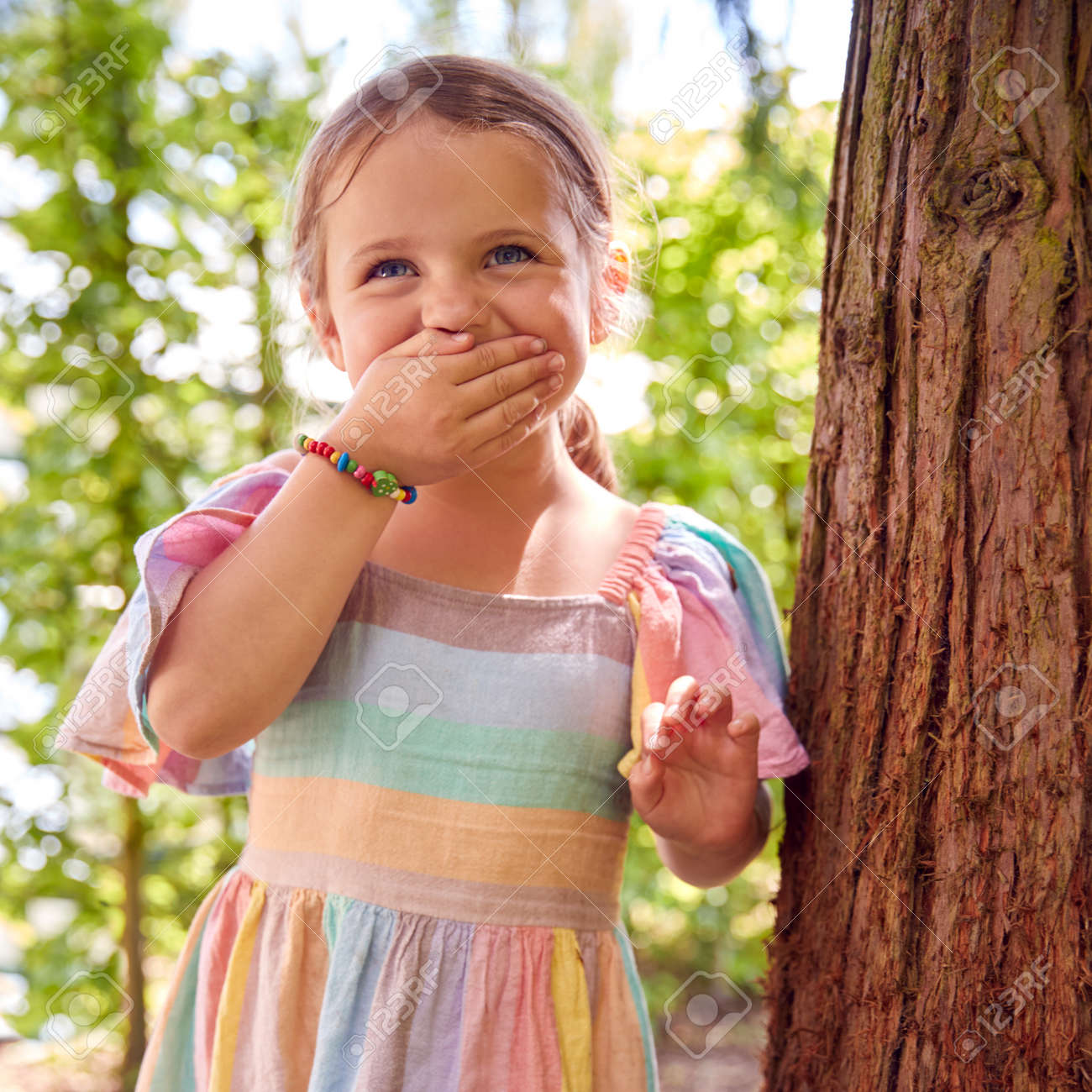 Smiling Young Girl Playing Hide And Seek Behind Tree In Garden - 172365304