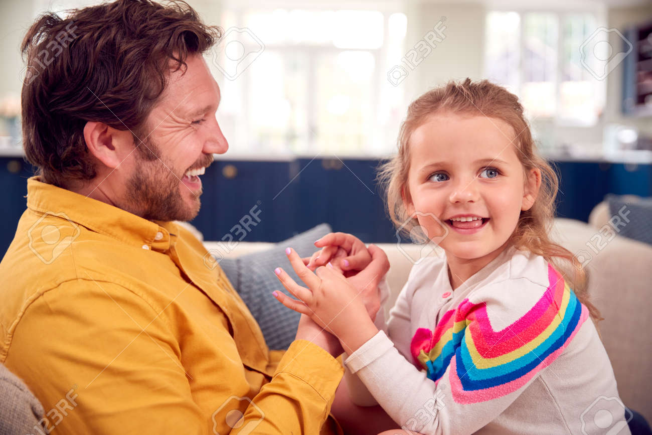 Father Painting Young Daughter's Nails As They Sit On Sofa Together - 172365329