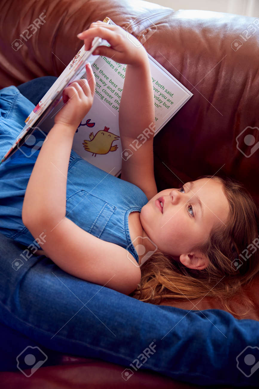 Close Up Of Father And Daughter Lying On Sofa At Home As Girl Reads Book - 172365341