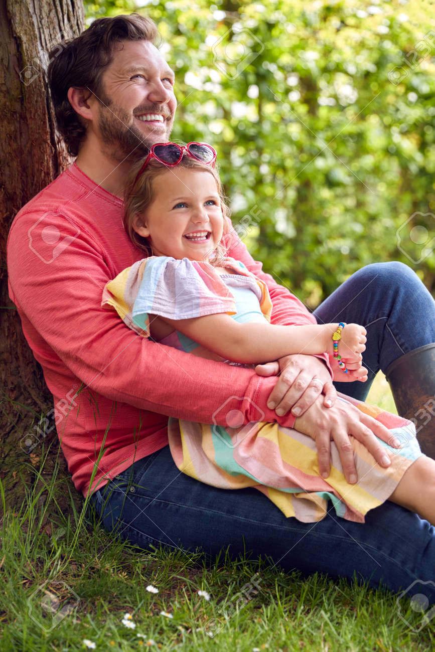 Loving Father Cuddling Young Daughter Sitting Under Tree In Garden Together - 172365342