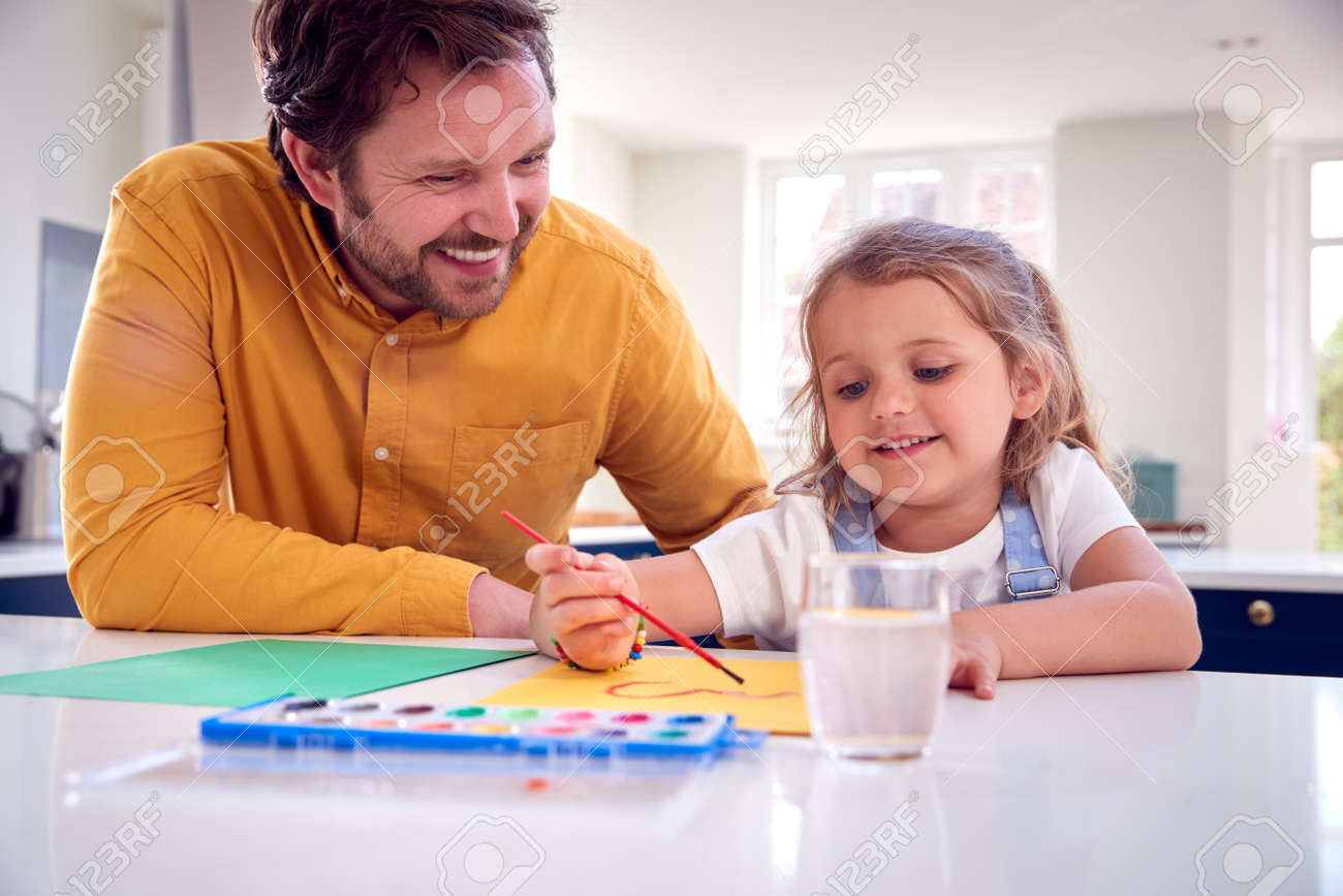 Father And Daughter Painting Picture On Kitchen Counter - 172365347