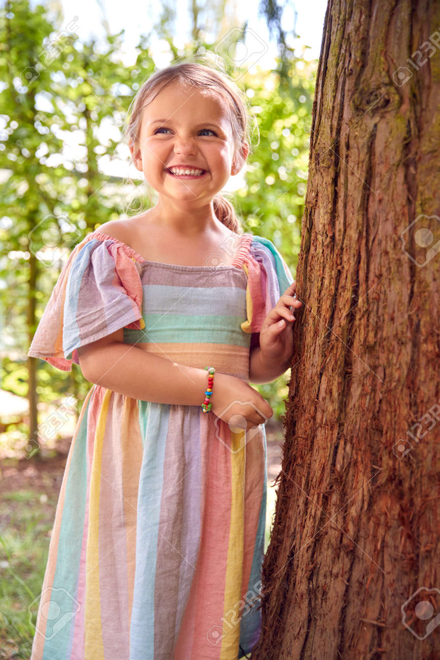 Smiling Young Girl Playing Hide And Seek Behind Tree In Garden - 172365350