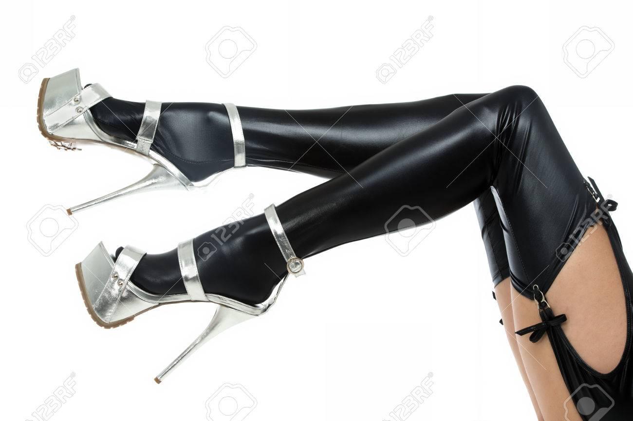 c64e4b633f Foto de archivo - Las piernas de una mujer en ropa fetichista  látex medias  con liguero y zapatos de tacones altos con plataforma extrem.