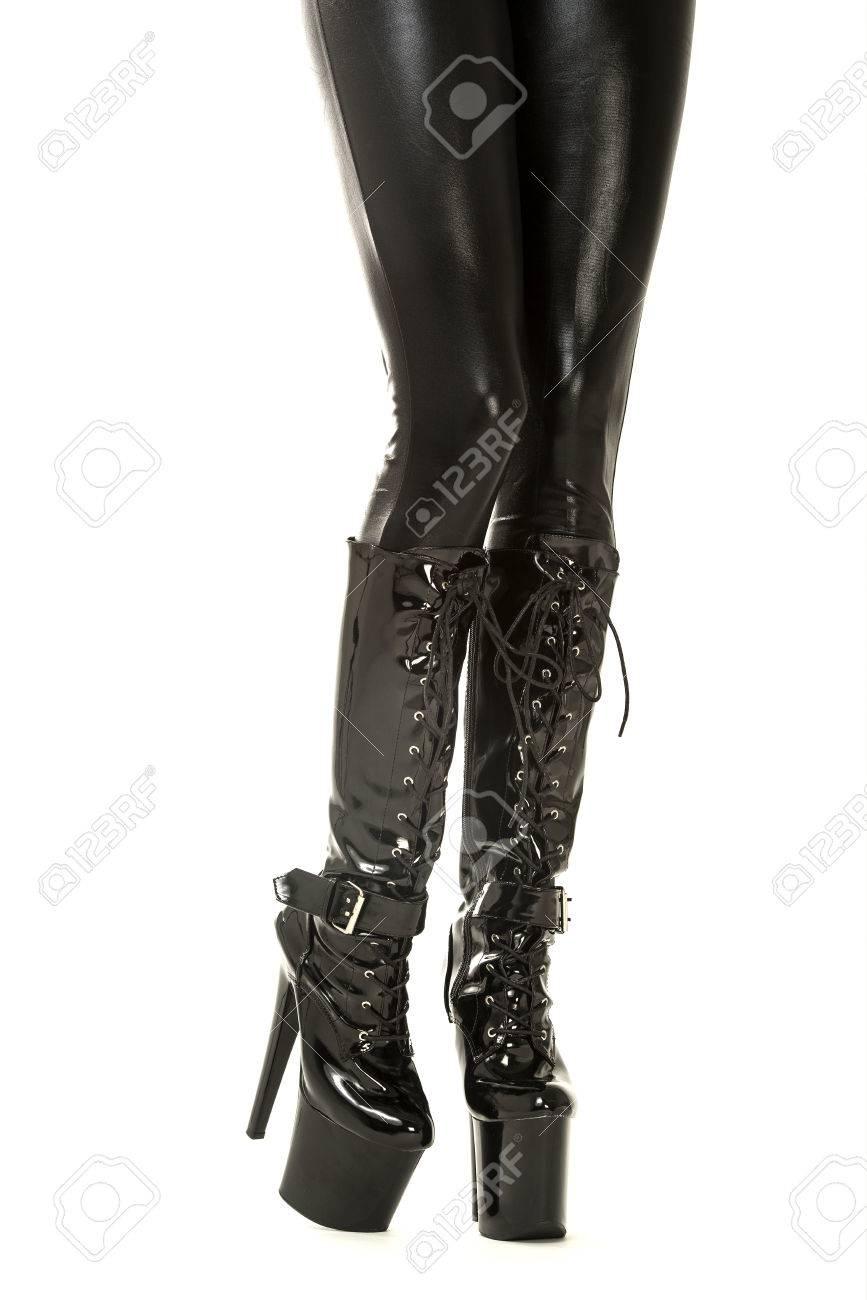 24421a1989 Foto de archivo - Las piernas de una mujer en ropa fetichista  látex medias  con liguero y tacones botas altas con plataforma extrem.