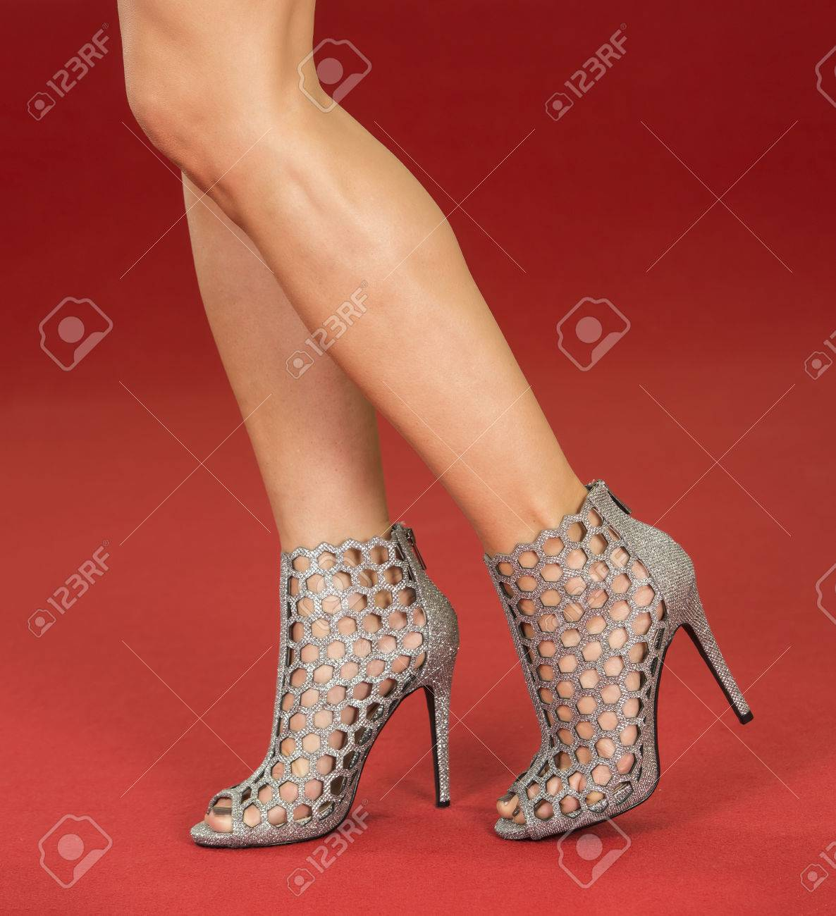 1d5052534cb7 Sexy legs of a woman wearing high heels ankle boots in silver metallic  design on a
