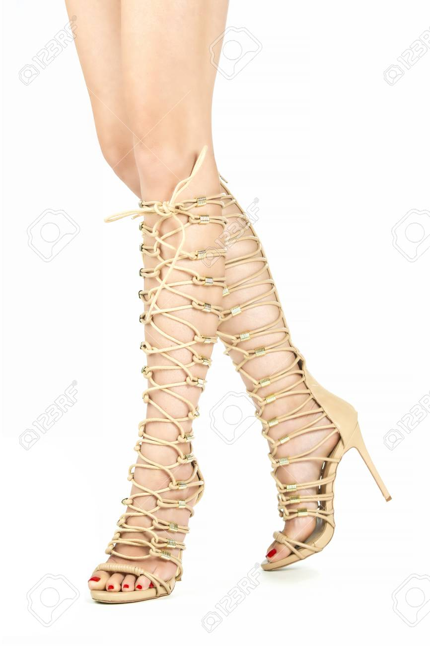23ece92f8f5 Long female legs in strappy high heels summer boots in nude color.