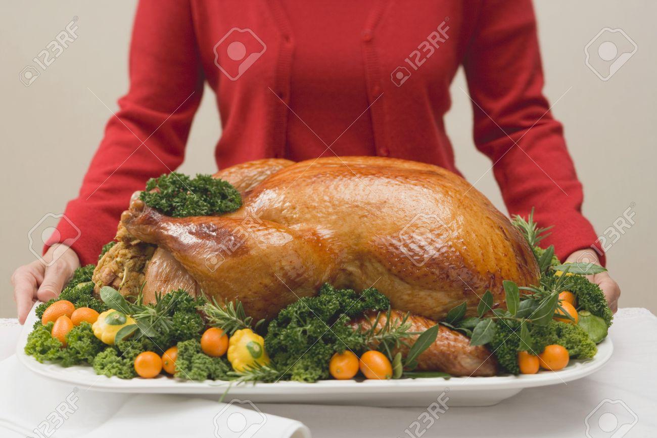 Stock Photo Woman Holding Roast Turkey On Large Platter