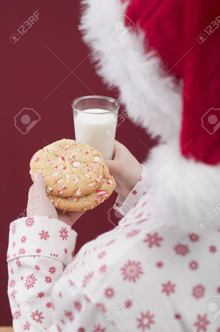 Foto de archivo - Mujer en el sombrero de Papá Noel que sostiene galletas y  vaso de leche 82130605b22