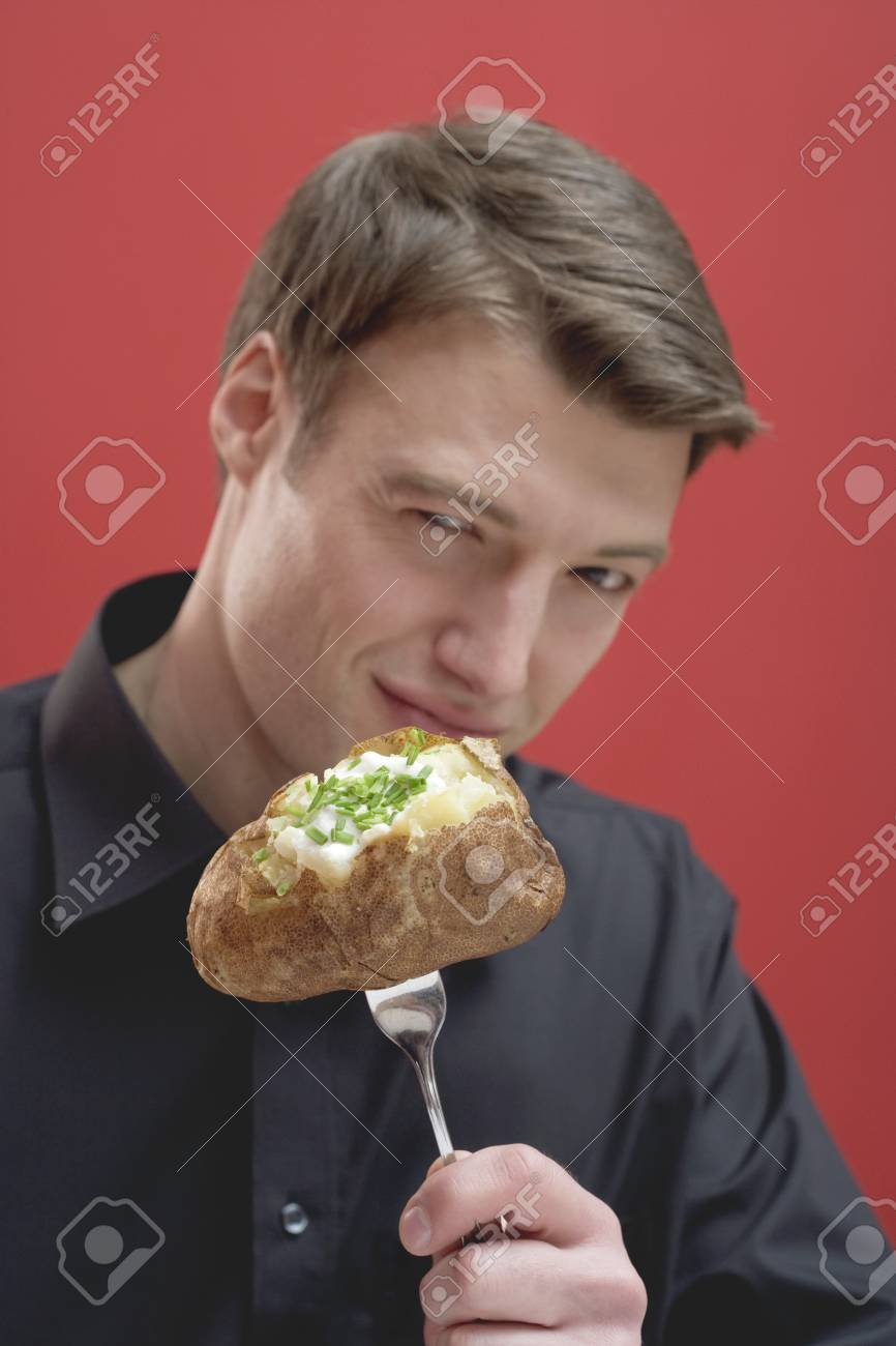 Man holding baked potato on fork