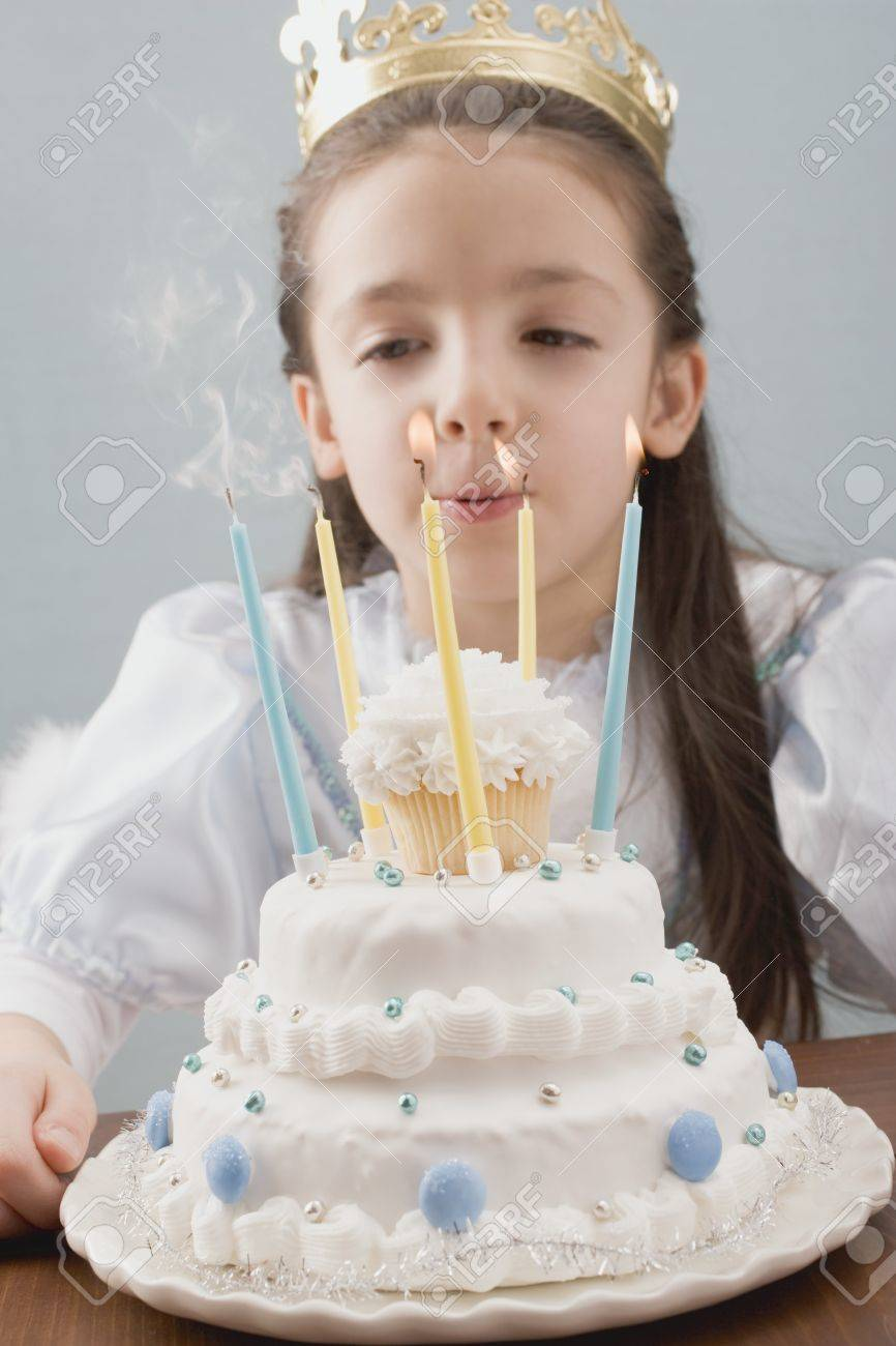 Little Princess Blowing Out Candles On Birthday Cake Stock Photo