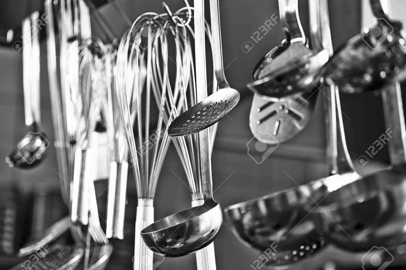Restaurant Kitchen Utensils cooking utensils hanging in a restaurant kitchen stock photo