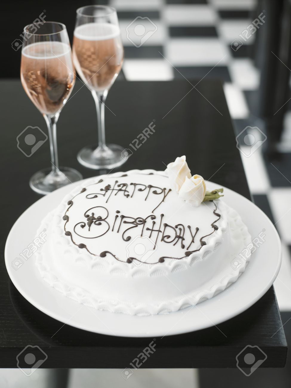 A White Birthday Cake And Ros Champagne Stock Photo