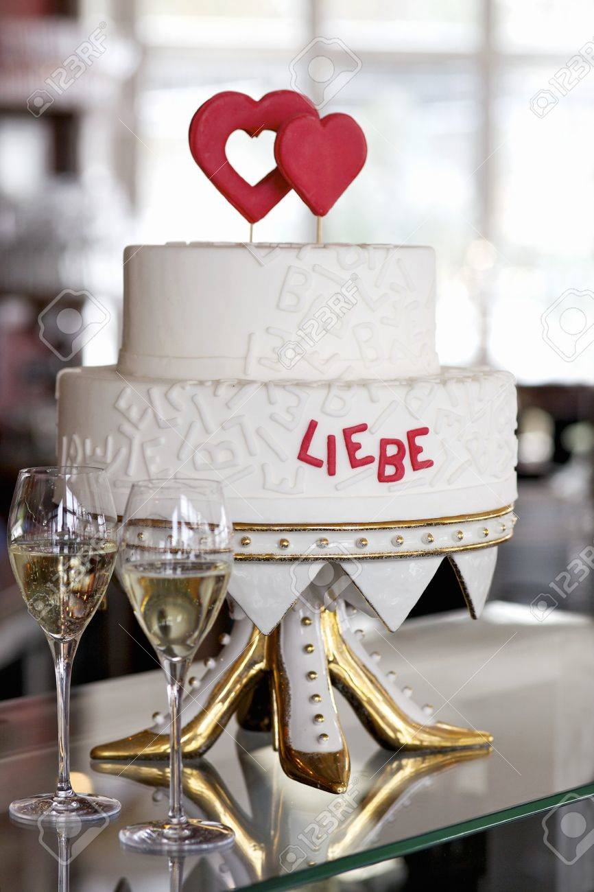 A Two Tier Wedding Cake With Red Hearts And Red Writing On An Unusual Cake