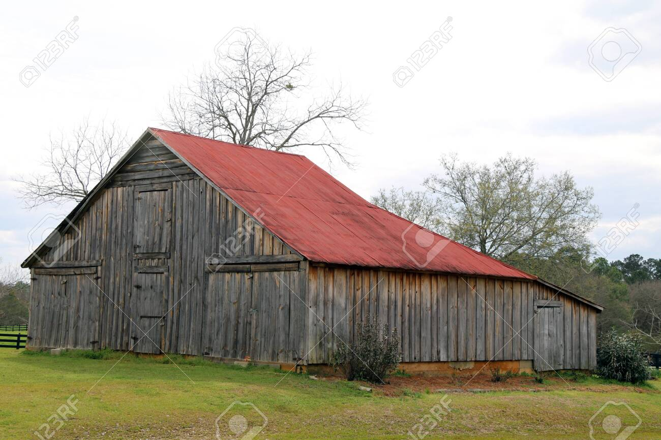 a retro farm barn with a red roof in an empty field - 144257785
