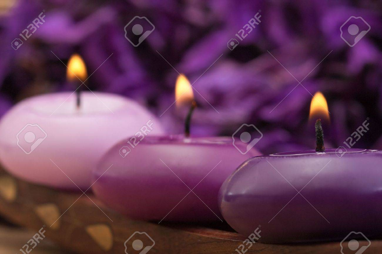 three burning purple toned candles with purple background Stock Photo - 6866420