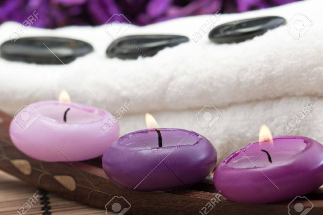 black hotstones on white towel with purple candles (2) Stock Photo - 6866418