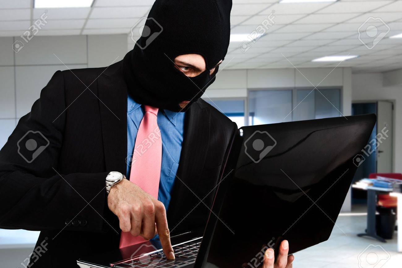 Hacker retrieving data from a laptop Stock Photo - 14748481