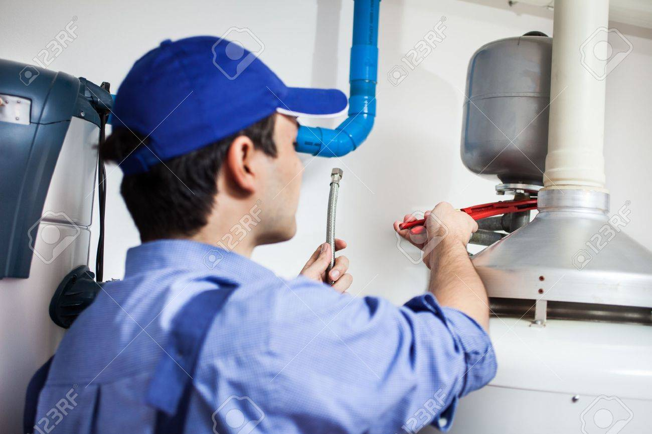 Plumber repairing an hot-water heater - 15271669