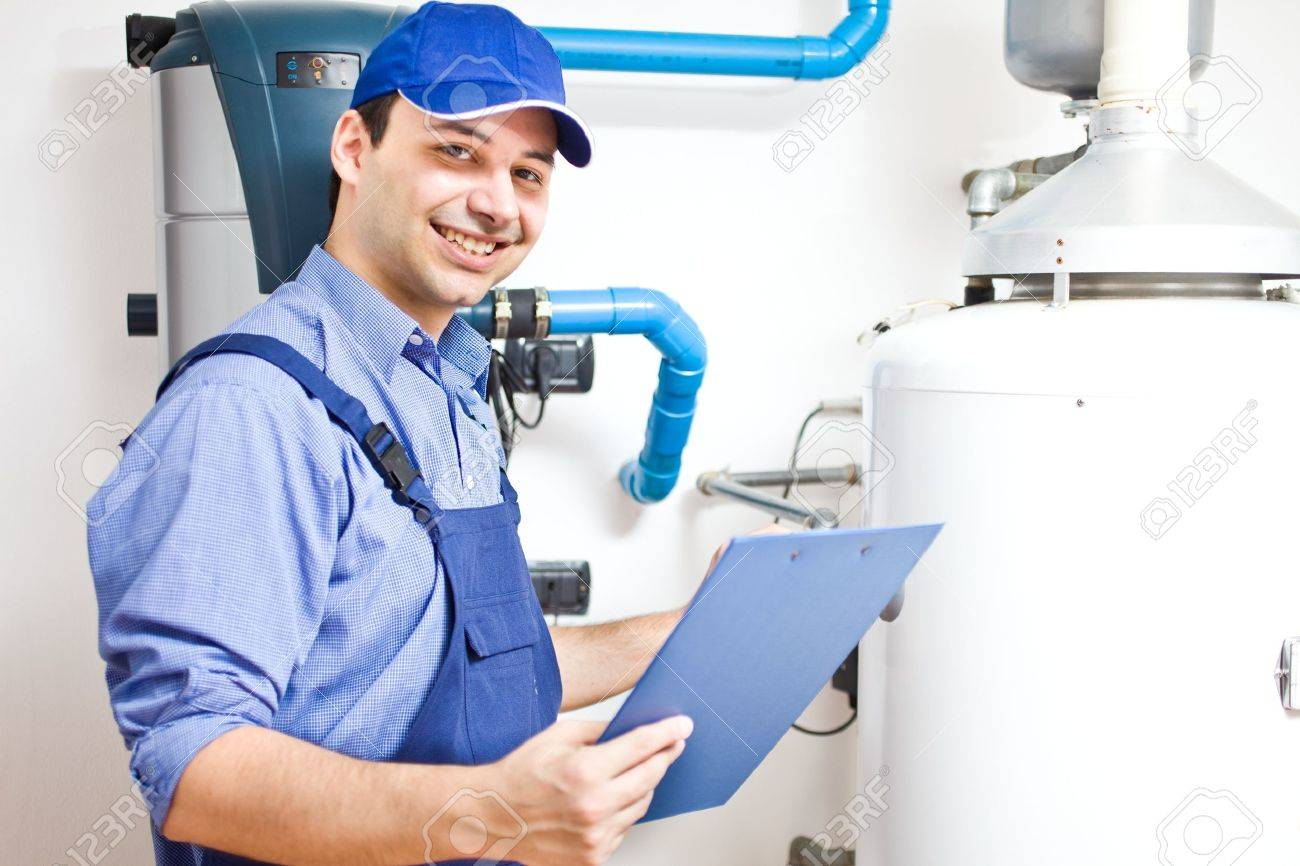 Smiling technician servicing an hot-water heater Stock Photo - 15174180