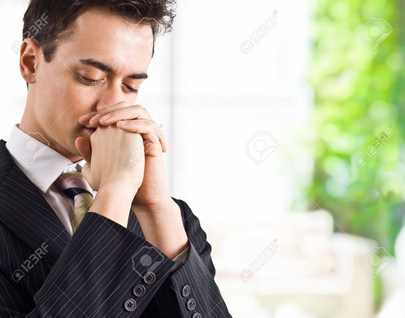 Young handsome business man praying Stock Photo - 15265054