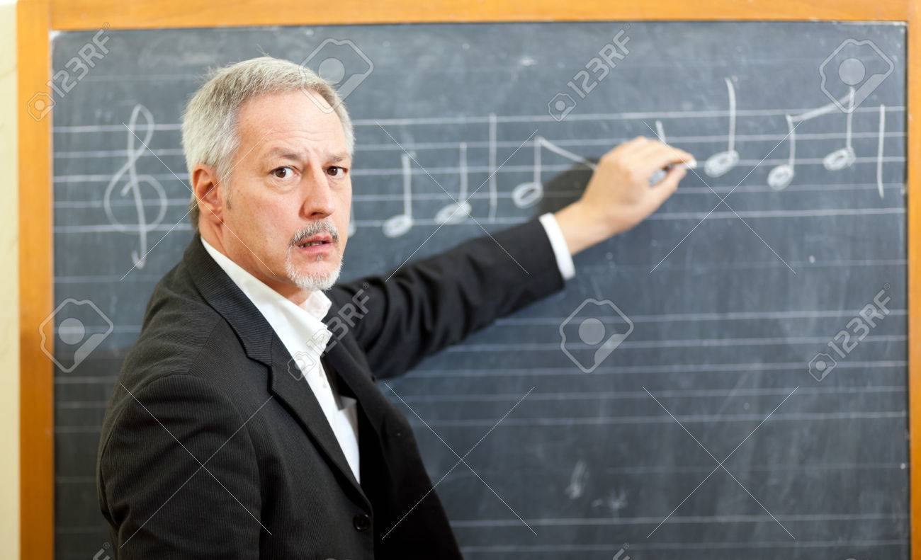 Music Teacher Writing Notes On A Blackboard Stock Photo, Picture ...