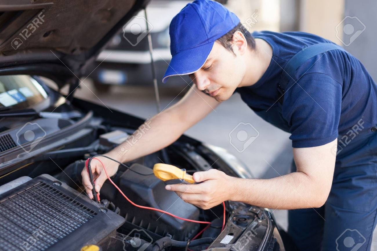 Auto electrician troubleshooting a car engine Stock Photo - 31043498
