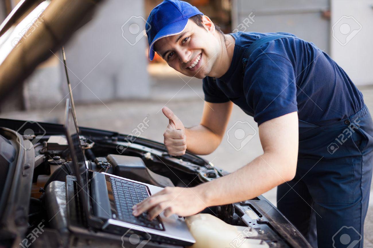 Lächelnd Mechaniker Mit Einer Laptop-Computer, Ein Auto Motor ...