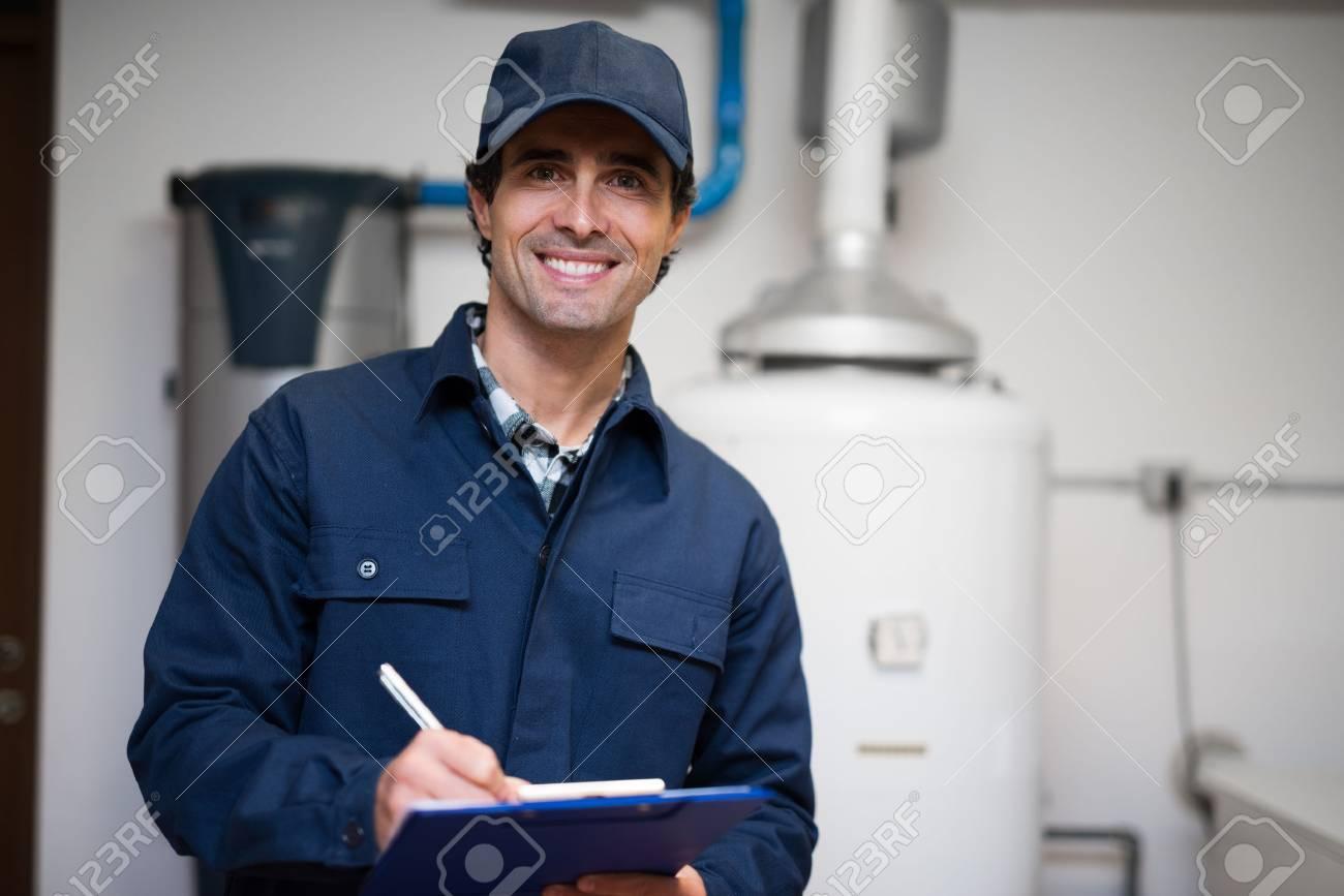 Technician servicing an hot-water heater - 55652950