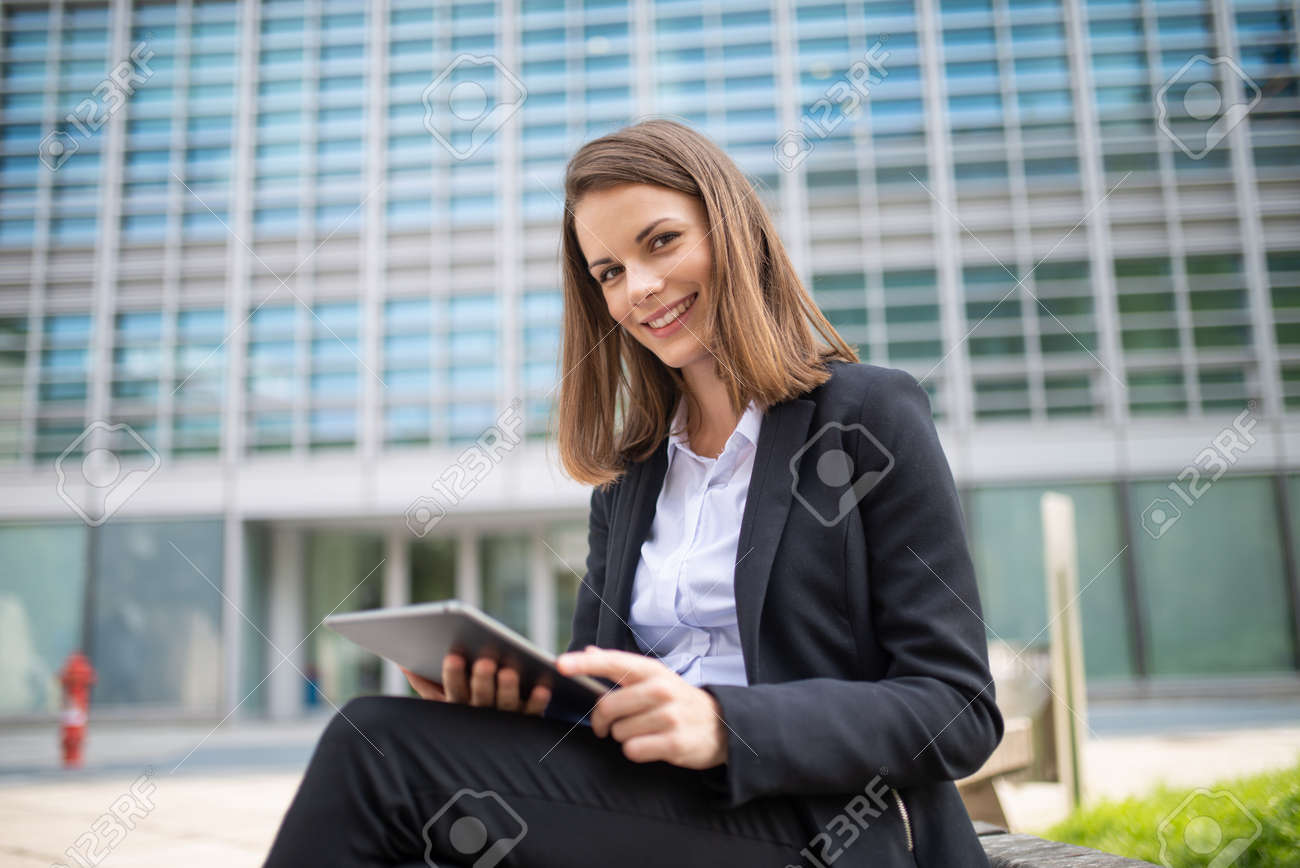Smiling businesswoman using a digital tablet outdoor sitting on a bench - 154239821