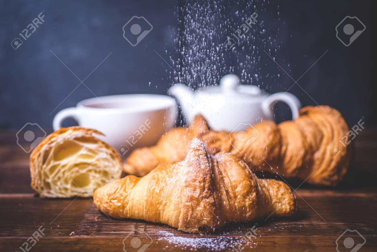 Sugar powder pours on the croissant. - 92865515
