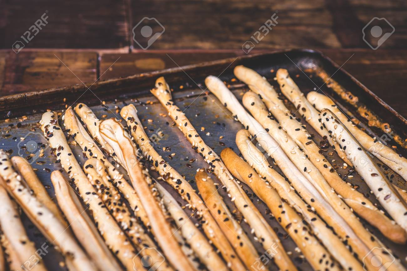 Bread sticks and a baking tray are strewn with seeds. - 92865377