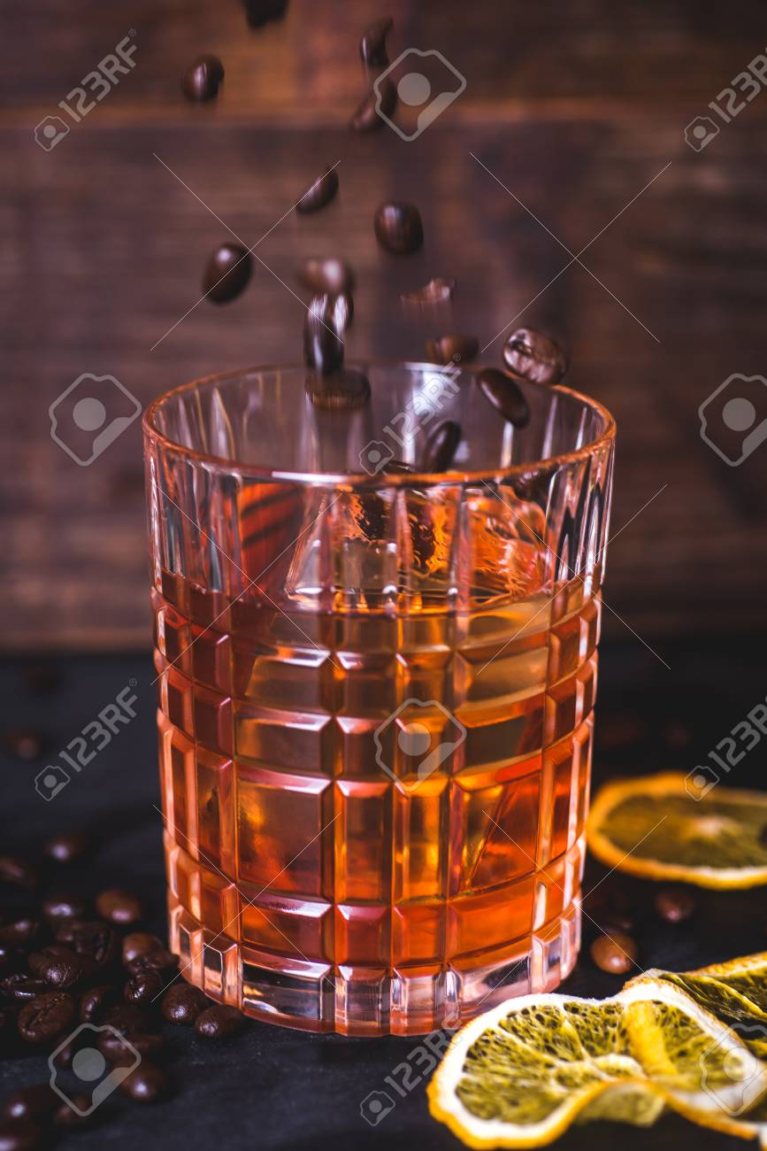 Grains of coffee fall into a glass with a drink. - 92865817