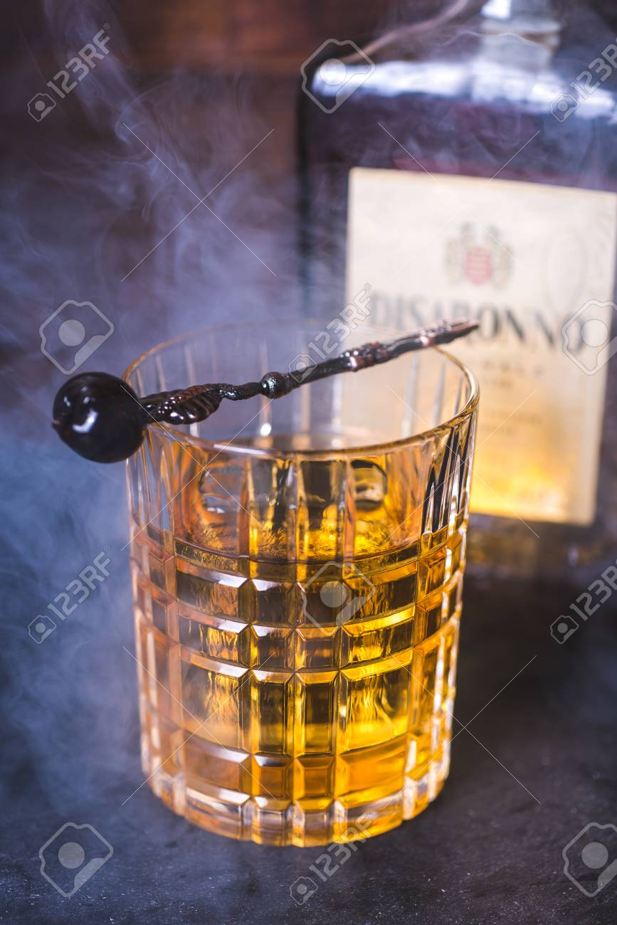 A glass with an alcoholic beverage in the smoke. - 92864066