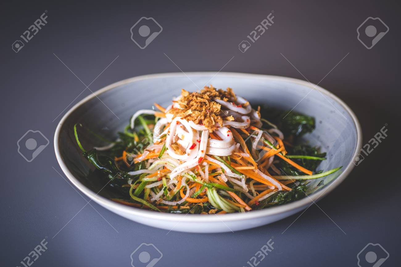 Salad from pickled vegetables and seafood. A light deep dish stands on a blue surface. - 93005376