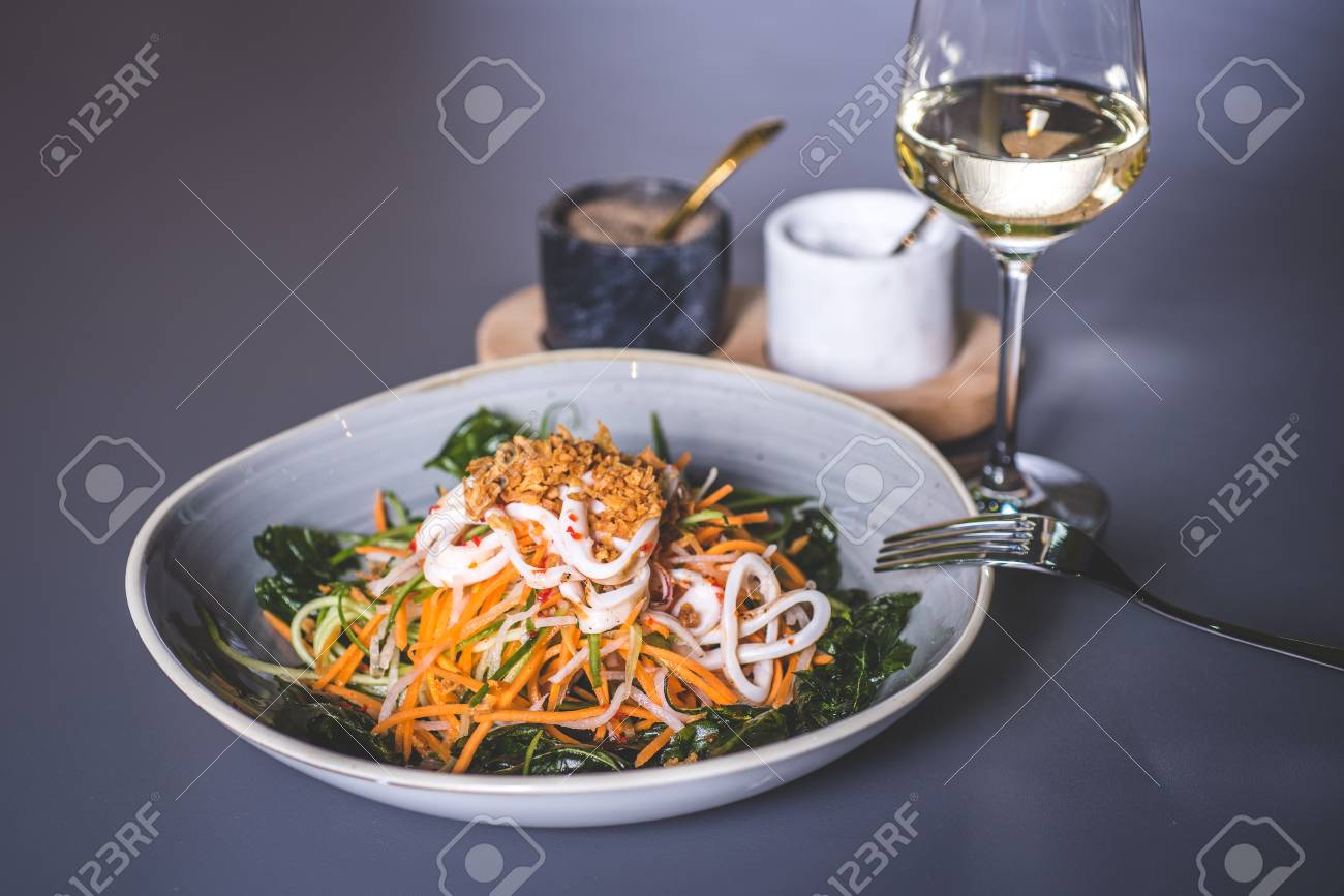 A fork lies on the edge of a plate with a salad. Salad with sea kale and seafood in a ceramic plate. Fougeres with white wine stands on the surface. Marble glasses with spices in the background. - 93005389