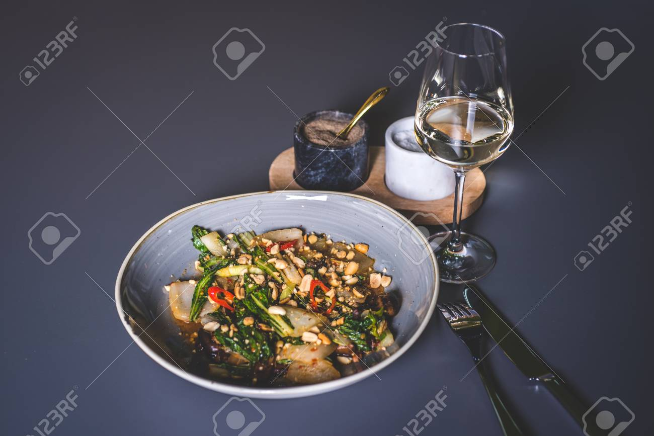 Salad with meat and peanuts with sauce. The knife and fork lie next to the plate. Fougeres with white wine stands on the surface. Marble glasses with spices in the background. - 92996492
