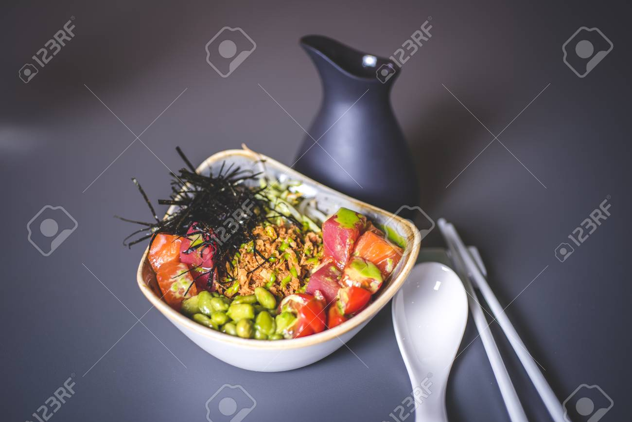 View of the salad with rice and sea cabbage. Square ceramic plate with sea kale and meat. Ceramic rods and a large spoon lie on the surface. A black jar is behind. - 92996442