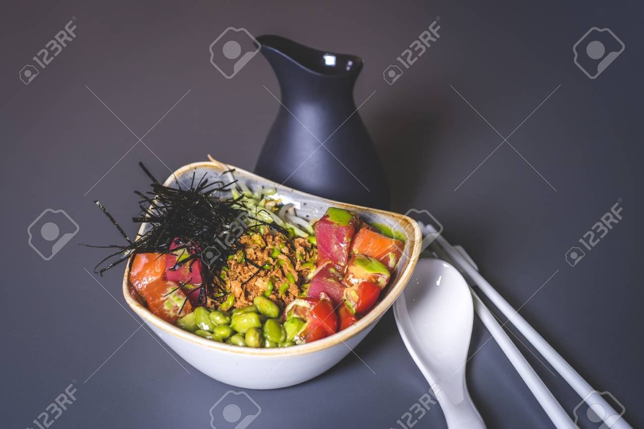 A view of a black jug and a salad of Asian cuisine in a square plate. View of the salad with rice and sea cabbage. Square ceramic plate with sea kale and meat. Ceramic rods and a large spoon lie on the surface. A black jar is behind. - 92996493