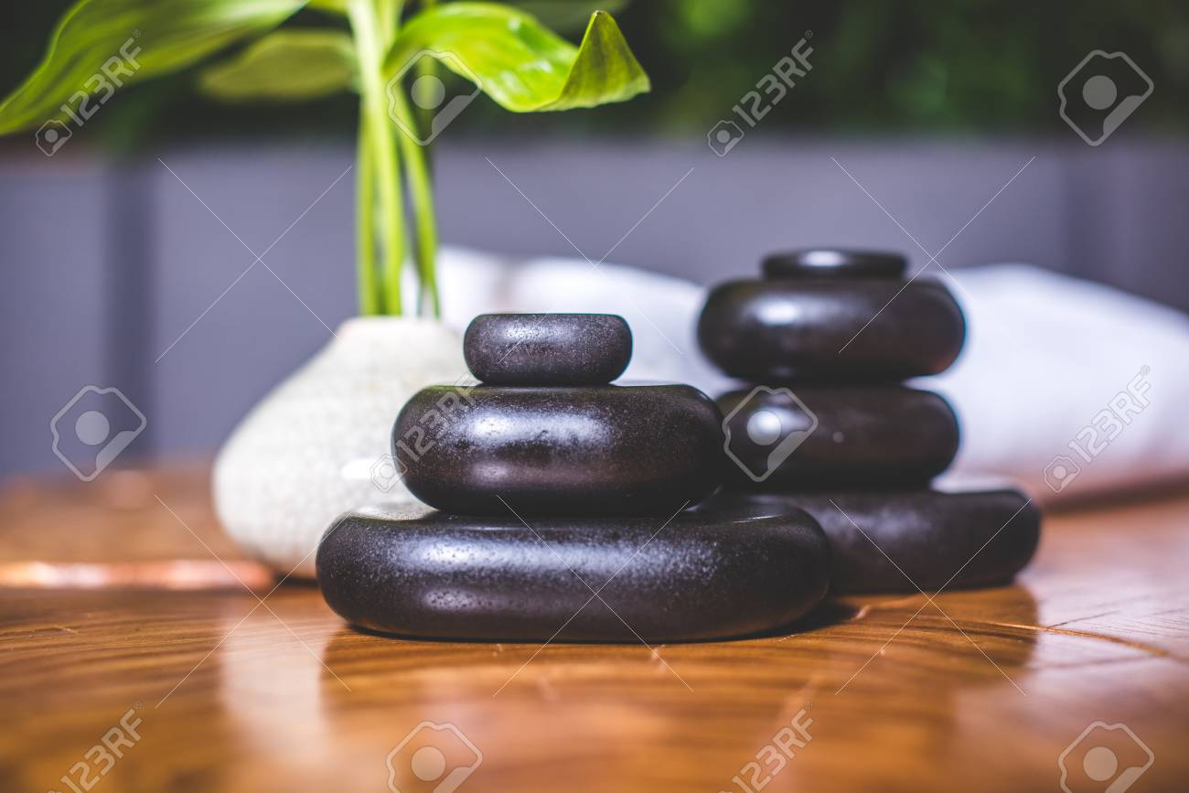 Pyramid of dark stones for massage close-up. Pyramids of stones for massage lie on the table. White towels lie in the background. - 94050153