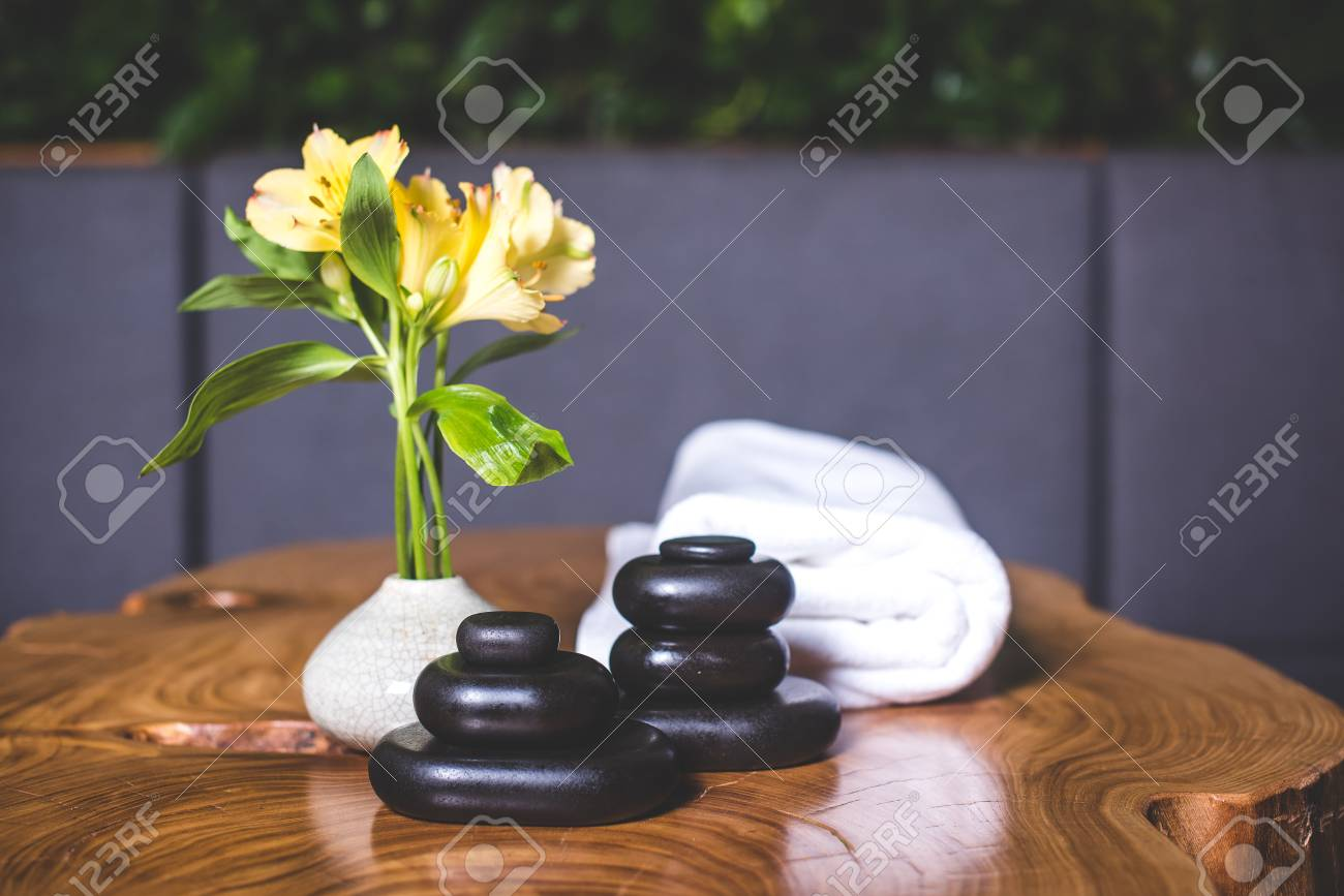 Yellow daffodils stand in a white vase. Pyramid of dark stones for massage close-up. Pyramids of stones for massage lie on the table. White towels lie in the background. - 94135533
