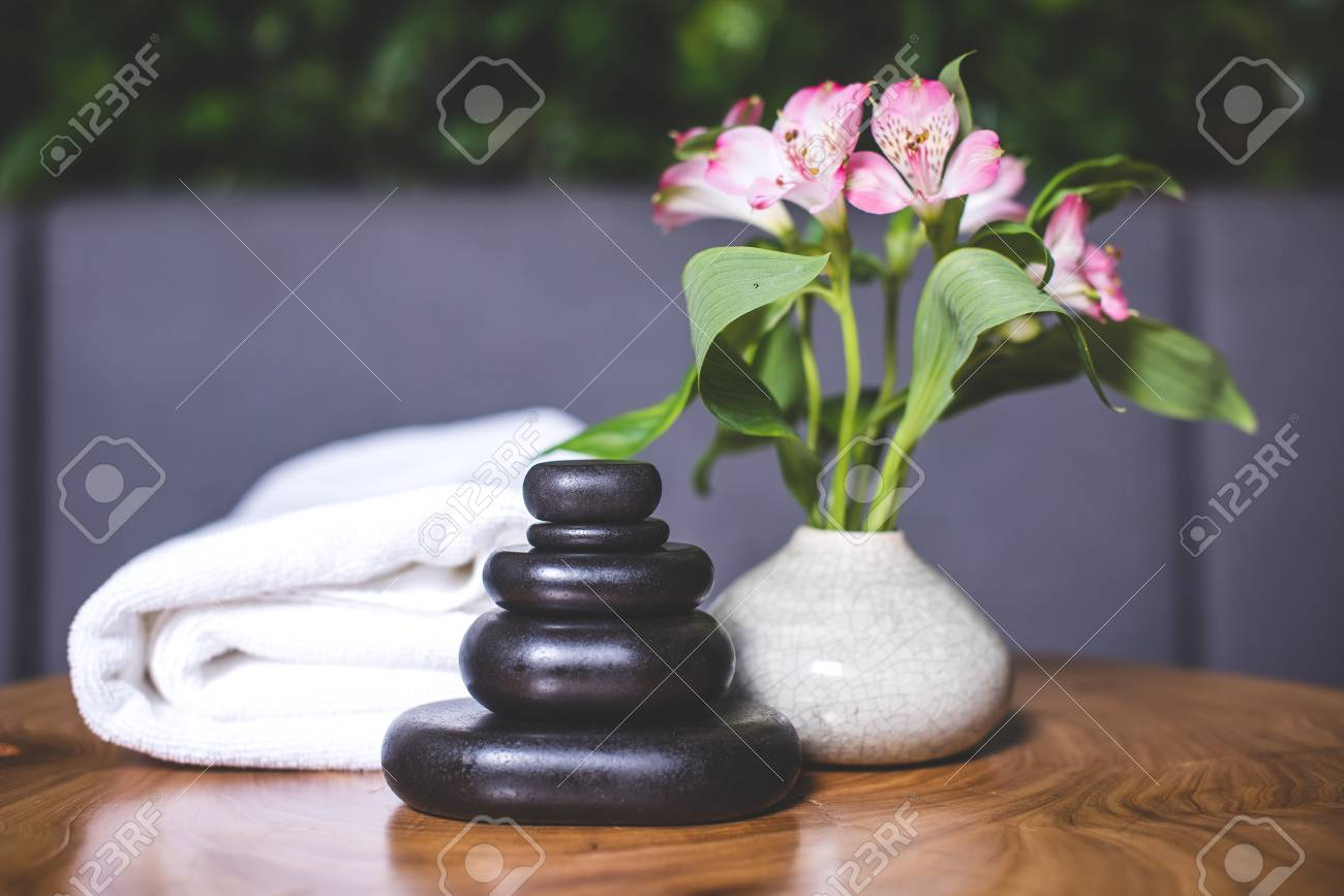 Dark stones for massage are stacked on top of each other on the table. White-pink daffodils stand in a white vase. Pyramids of stones for massage lie on the wooden table. White towels lie in the background. - 94135536