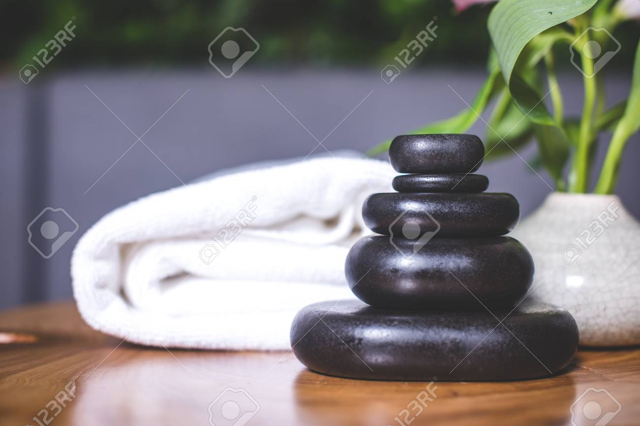 Close-up on dark stones for massage on a wooden table. White towels lie in the background. - 94135537