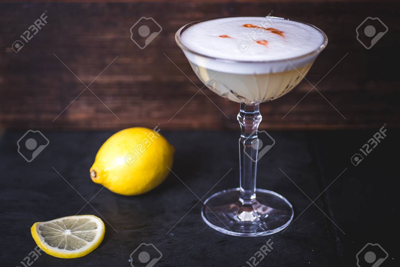 Lemon and lemon slice lies near the wine glass. - 99534741