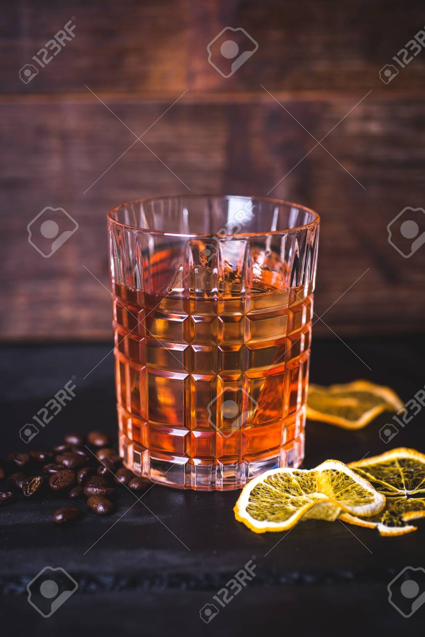 A glass with whiskey on a wooden background. - 99534755