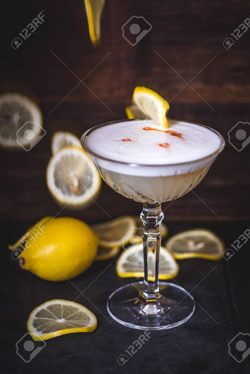 Lemon slices fall into a cocktail. - 99535047