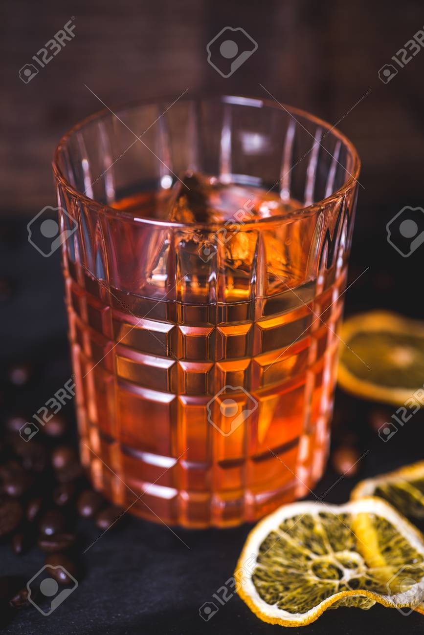 An ice cube floats in alcohol in a glass. - 99538273